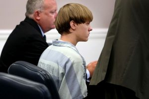 Dylan Roof (C), the suspect in the mass shooting that left nine dead in a Charleston church last month, appears in court July 18, 2015 in Charleston, South Carolina. The Associated Press, WCIV-TV and The Post and Courier of Charleston are challenging a judge's order issued last week that prohibits the release of public records in the June 17 shooting at Emanuel African Methodist Episcopal church. (Photo by Grace Beahm-Pool/Getty Images)