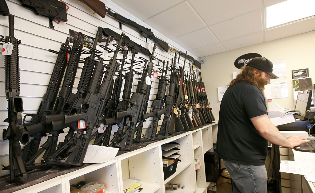 A row of guns many that are AR-15's line the wall as owner of Ready Gunman, Willy Ludlow, works on paperwork on June 17, 2016 in Springville, Utah. (Photo by George Frey/Getty Images)